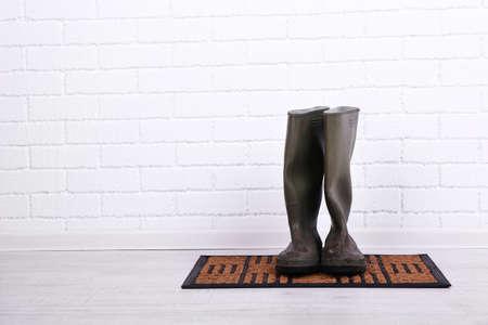 Dirty wellington boots on door mat in room photo