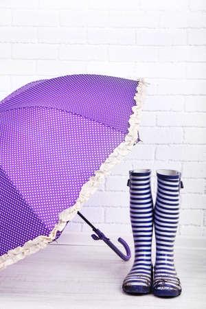 wellington: Dirty wellington boots with umbrella on floor in room Stock Photo