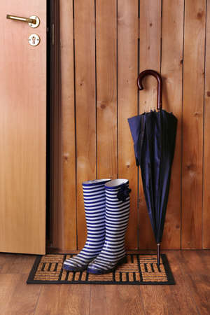 forecaster: Dirty wellington boots with umbrella on door mat in room