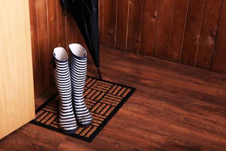 Dirty wellington boots with umbrella on door mat in room photo