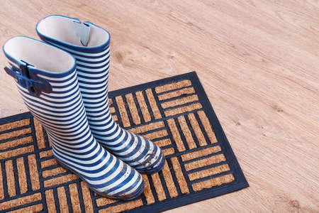 forecaster: Dirty wellington boots on door mat in room Stock Photo