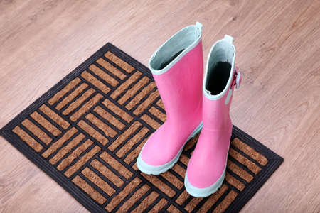 forecaster: Pink wellington boots on door mat in room Stock Photo