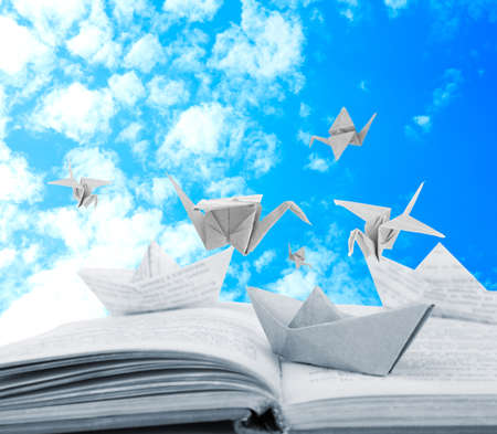 Origami boats and cranes on book on sky background photo