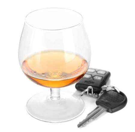 under the influence: Glass of alcoholic drink and car key, isolated on white
