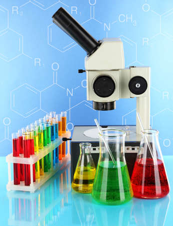 Test tubes with colorful liquids and microscope on blue background photo