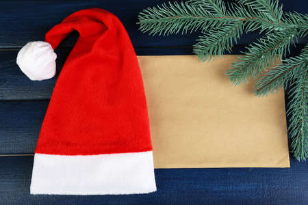 Santa red hat with branch of fir-tree and sheet of paper on color wooden background photo