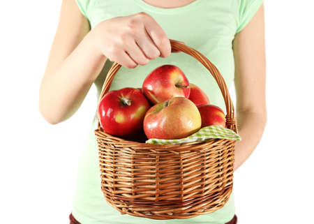 Woman holding red apples in wicker basket on white background photo