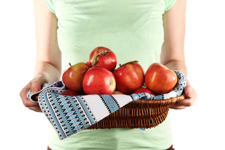 Woman holding red apples in wicker basket with napkin on white background photo