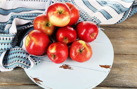 dish cloth: Heap of apples on board with dish cloth on wooden table background
