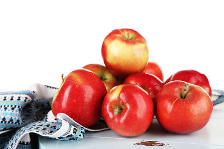 dish cloth: Heap of apples on board with dish cloth on wooden table isolated on white background Stock Photo