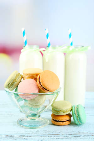 Gentle colorful macaroons and milk bottles on color wooden table, light background photo