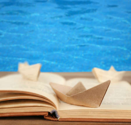 Origami boats on old book on sea background photo