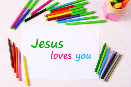 loves: Jesus loves you text on paper on table background