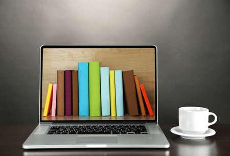 biblioteca: Concepto del aprendizaje electr�nico. Biblioteca digital - libros en el interior del ordenador port�til Foto de archivo