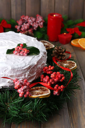 Christmas cake with wreath on wooden background photo