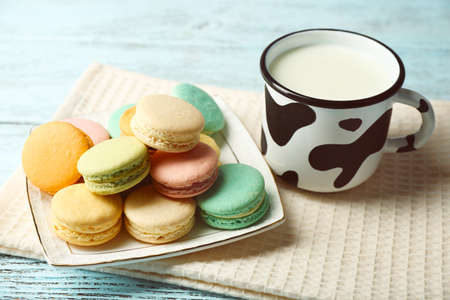 Gentle colorful macaroons and milk in mug on color wooden background photo