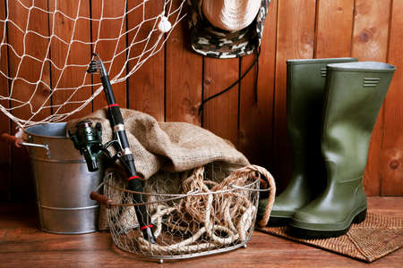 fishing equipment: Fishing equipment on wooden wall background, indoors Stock Photo