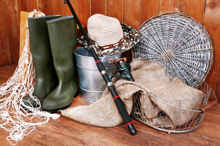 Fishing equipment on wooden wall background, indoors Stock Photo