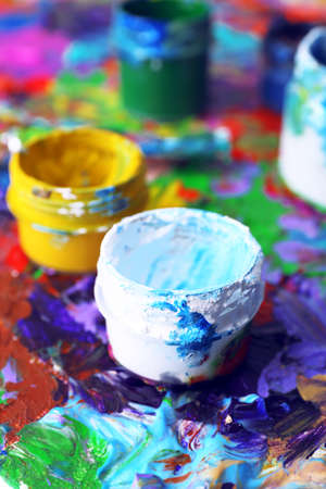 Cans of paint on colorful painted background photo
