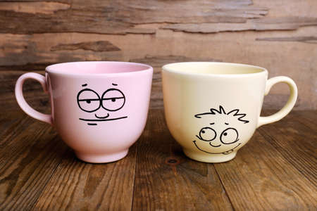 opinionated: Emotional cups on wooden background