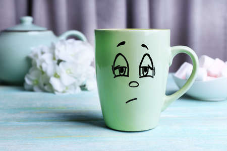 opinionated: Emotional cup on wooden table Stock Photo