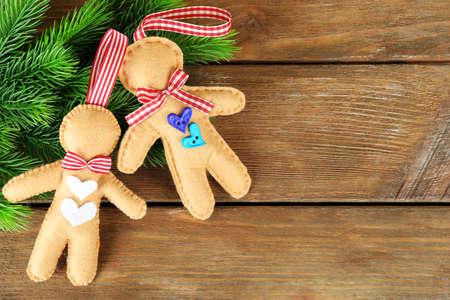 Handmade felt gingerbread men and fir tree bud on wooden background photo