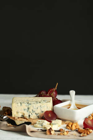 Still life with tasty blue cheese on table, on dark background photo