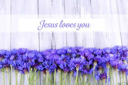 jezus: Piękne chabry i tekst Jezus cię kocha na drewnianym tle