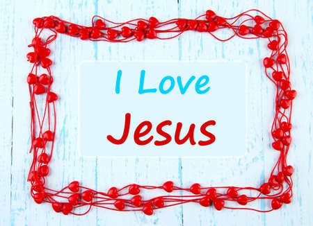 I love Jesus text in hearts beads frame on wooden background photo