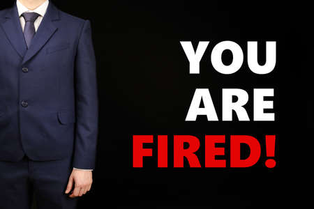 you are fired: Businessman and text You Are Fired on black background