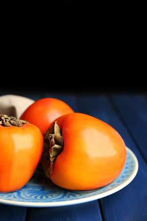 astringent: Ripe sweet persimmons, on wooden table