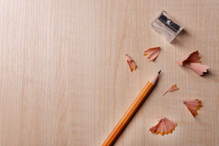 shavings: Pencil with sharpening shavings on wooden background