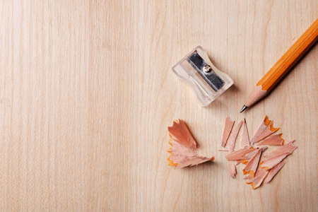 sharpening: Pencil with sharpening shavings on wooden background