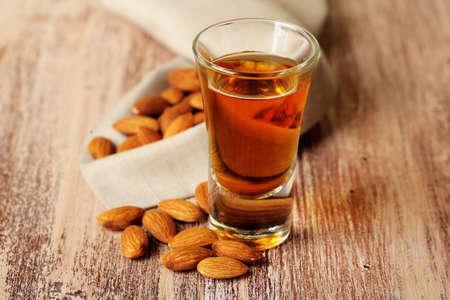amaretto: Dessert liqueur Amaretto with almond nuts, on wooden table Stock Photo