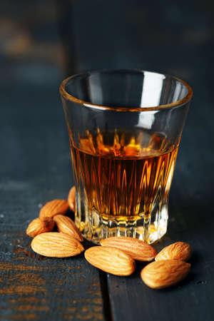 amaretto: Dessert liqueur Amaretto with almond nuts, on dark wooden table