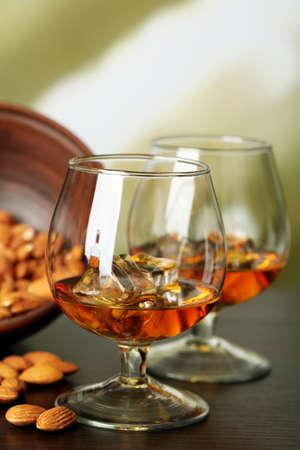 amaretto: Dessert liqueur Amaretto with almond nuts, on wooden table, on light background