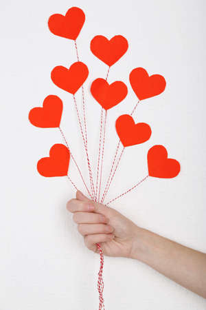 celebration party: Female hand holding paper balloons, on white wall background Stock Photo