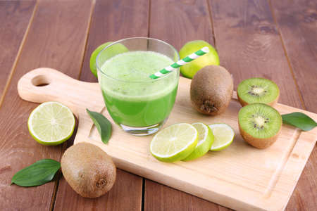 kiwi: Glass of fresh lime juice with pieces of lime and kiwi on cut board and wooden table background