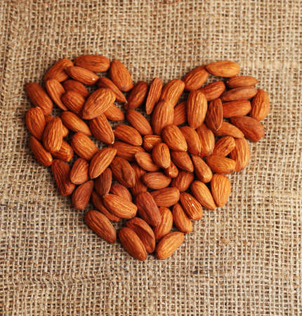 healthy grains: Almonds on sackcloth background