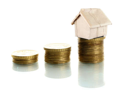 Small house standing on stack of coins isolated on white photo