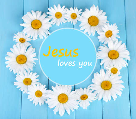 loves: Chamomile wreath and text Jesus loves you on blue wooden background