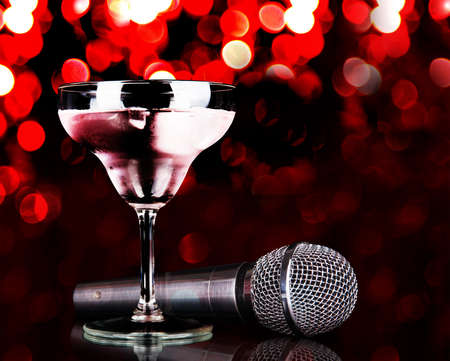 Silver microphone and cocktail on table on red lights background Archivio Fotografico