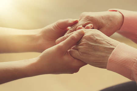elderly adults: Old and young holding hands on light background, closeup