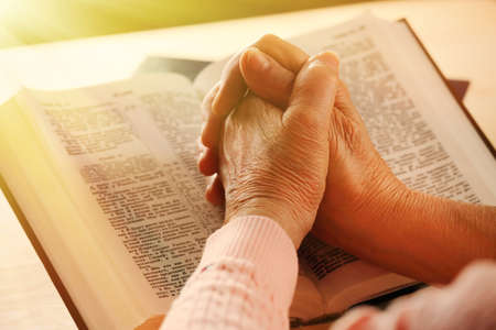 Hands of old woman with Bible on table, close-up photo