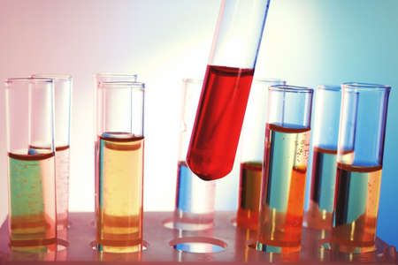 Test tube filled with red liquid on background of other tubes, close-up photo