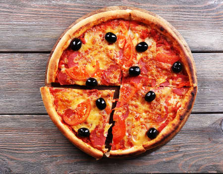 Delicious Italian pizza with black olives on wooden table background photo