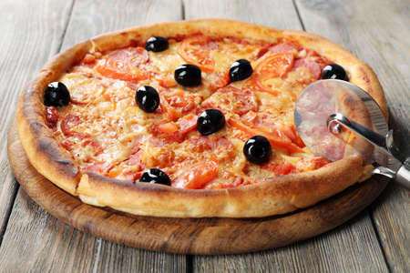 Tasty pizza with black olives and round knife on board and wooden table background photo