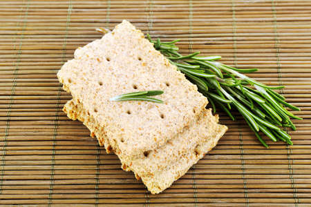 sprigs: Crispbread with sprigs of rosemary on bamboo mat background Stock Photo