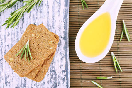 Crispbread with sprigs of rosemary on wooden cutting board and spoon of oil on bamboo mat background photo