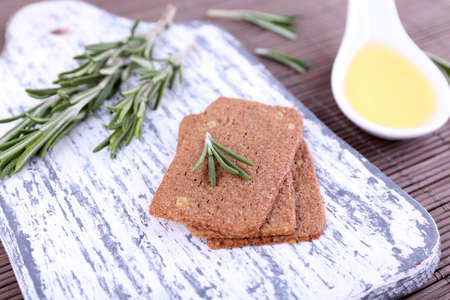 sprigs: Crispbread with sprigs of rosemary on cutting board and spoon of oil on bamboo mat background